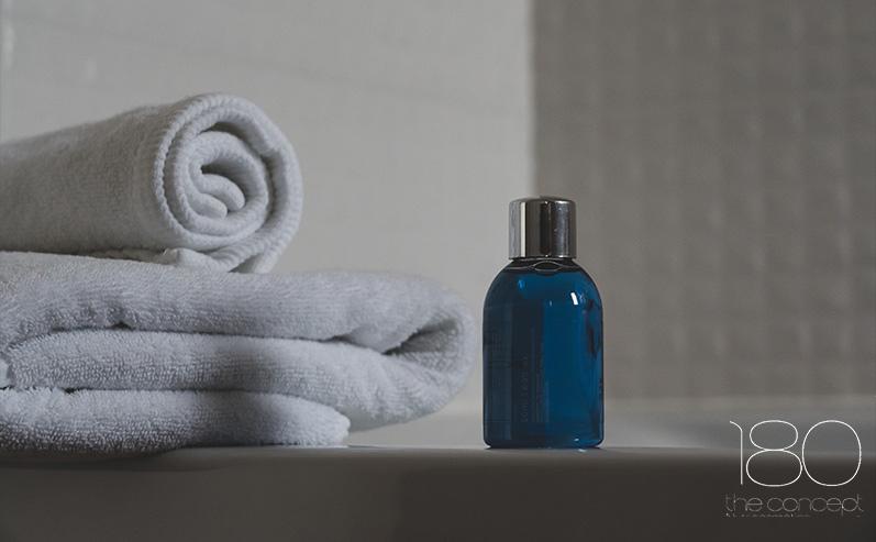 blue-glass-bottle-beside-white-towel